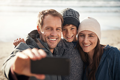 Buy stock photo Cropped shot of a happy young family standing together and taking a selfie with a cellphone at the beach
