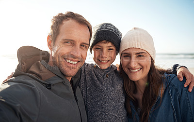 Buy stock photo Cropped portrait of an affectionate young family standing together and smiling during a day out on the beach