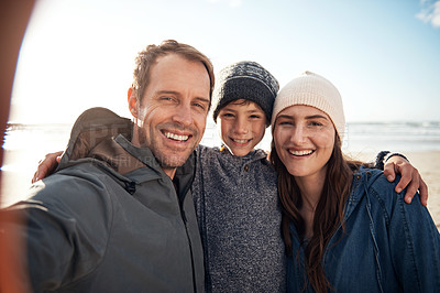 Buy stock photo Cropped portrait of a happy young family standing together and taking a selfie during a day out on the beach