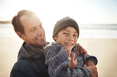 Buy stock photo Cropped portrait of a handsome young man hugging his son while bonding with him on the beach