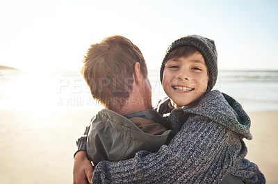 Buy stock photo Cropped portrait of an unrecognizable man hugging his son while bonding with him on the beach