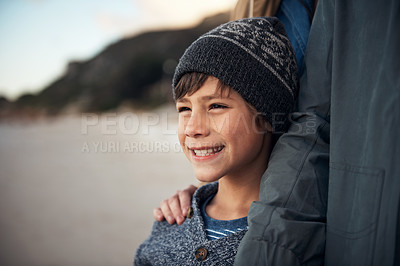 Buy stock photo Cropped shot of a happy young boy standing with his parent and enjoying a sunset on the beach