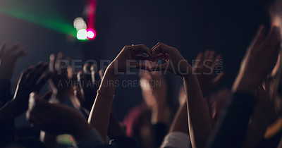 Buy stock photo Cropped shot of an unrecognizable young woman making a heart shape with her hands while dancing in a club