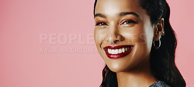 Buy stock photo Studio portrait of a beautiful young woman smiling while standing against a pink background