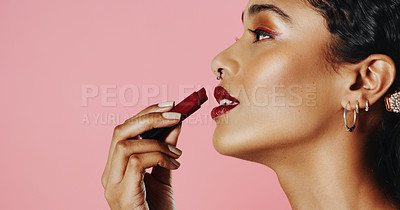 Buy stock photo Studio shot of a beautiful young woman applying lipstick while standing against a pink background