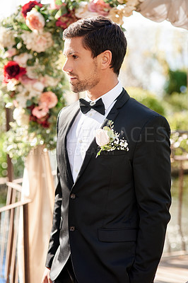 Buy stock photo Shot of a handsome young man standing by the aisle outdoors on his wedding day
