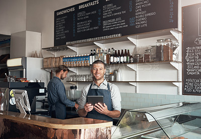Buy stock photo Portrait of a mature man using a digital tablet while working alongside a colleague in a cafe