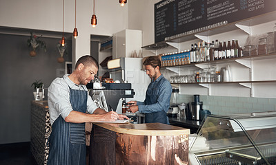 Buy stock photo Shot of a mature man writing on a clipboard while working in a cafe with his colleague in the background