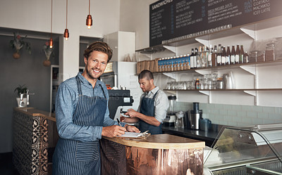 Buy stock photo Portrait of a young man writing on a clipboard while working in a cafe with his colleague in the background