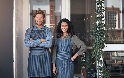 Buy stock photo Portrait of two coffee shop employees standing outside their cafe