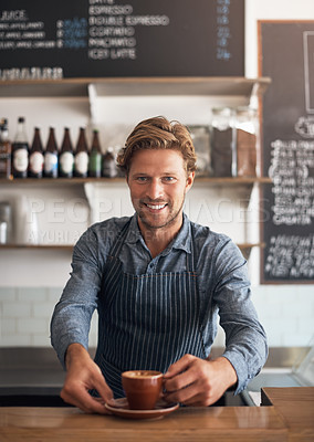 Buy stock photo Portrait of a young waiter serving a cup of coffee in a cafe