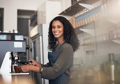 Buy stock photo Shot of a young woman operating a coffee machine in a cafe