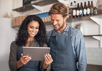Buy stock photo Shot of a young man and woman using a digital tablet while working in a cafe