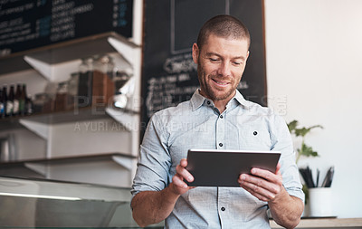 Buy stock photo Shot of a business owner using a digital tablet in his cafe