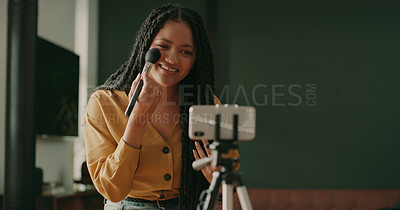 Buy stock photo Shot of an attractive young woman using her cellphone to record her beauty and makeup video blog at home