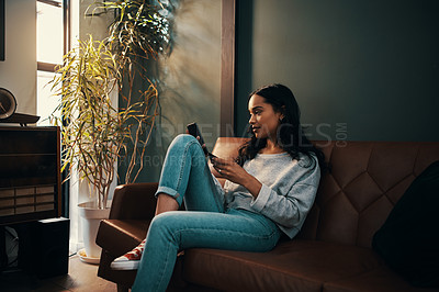 Buy stock photo Shot of an attractive young woman using her credit card and cellphone to shop online while relaxing at home