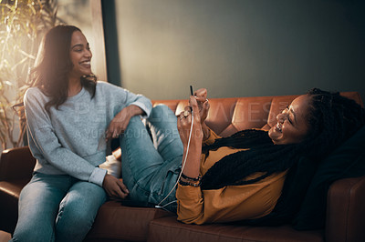 Buy stock photo Shot of two attractive young women using a cellphone while spending time and relaxing together at home