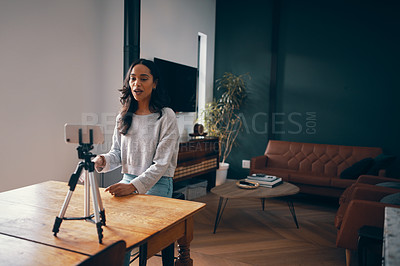 Buy stock photo Shot of an attractive young woman using a cellphone to record her video blog at home