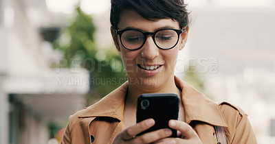 Buy stock photo Cropped shot of an attractive young businesswoman using a smartphone while standing in the city during the day