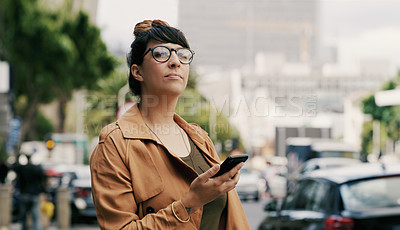 Buy stock photo Cropped shot of an attractive young businesswoman looking thoughtful while waiting for a cab in the city during the day