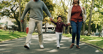 Buy stock photo Shot of a couple walking with their little son at the park