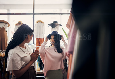 Buy stock photo Shot of a woman trying on a hat while shopping with her friend in a clothing store
