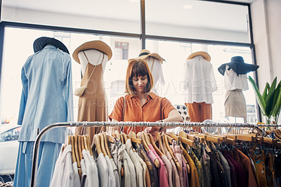 Buy stock photo Cropped shot of a young woman looking at items on a clothing rail in a boutique