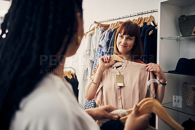 Buy stock photo Shot of a young woman holding up a garment while asking her friend's advice in a clothing store