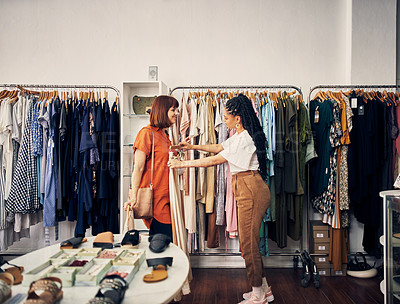 Buy stock photo Shot of two young women looking at garments in a clothing store