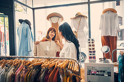 Buy stock photo Cropped shot of two young women looking at clothes on a clothing rail in a boutique