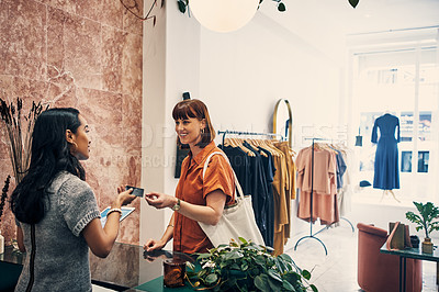 Buy stock photo Shot of a customer paying with a credit card in a clothing store