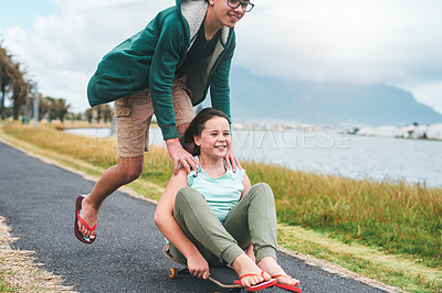Buy stock photo Cropped shot of a happy young boy pushing his little sister on his skateboard while they bond outdoors