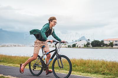 Buy stock photo Full length shot of a happy young boy riding his bicycle along the lagoon during a day out alone
