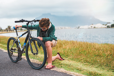 Buy stock photo Full length shot of a young boy kneeling next to a bicycle and trying to fix it while outdoors