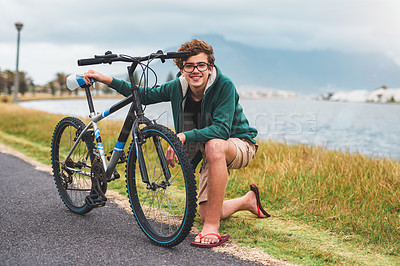 Buy stock photo Full length portrait of a happy young boy kneeling next to a bicycle and trying to fix it while outdoors
