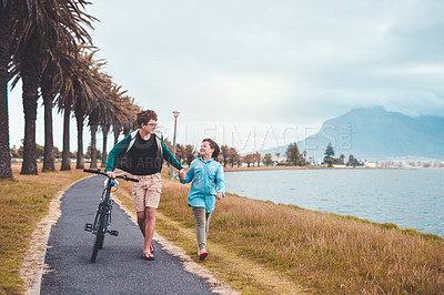 Buy stock photo Full length shot of two young children holding hands and walking alongside the lagoon together while pushing a bicycle