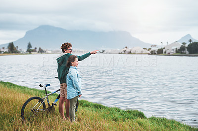 Buy stock photo Full length shot of two young children standing together and looking out at the lagoon during a bike ride outdoors