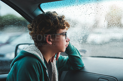 Buy stock photo Cropped shot of a young boy sitting and looking contemplative while looking out the car window during a rainstorm