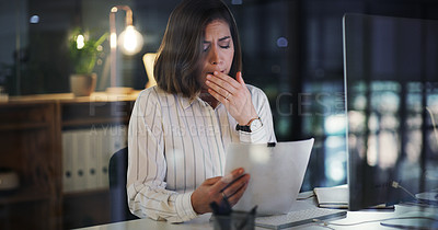 Buy stock photo Cropped shot of an attractive young businesswoman yawning while trying to read a document in her office at night