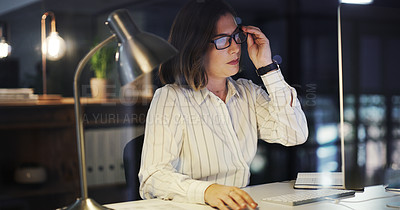 Buy stock photo Cropped shot of an attractive young businesswoman adjusting her spectacles while working late in a modern office
