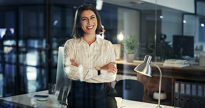 Buy stock photo Cropped portrait of an attractive young businesswoman smiling while standing with her arms crossed in a modern office at night