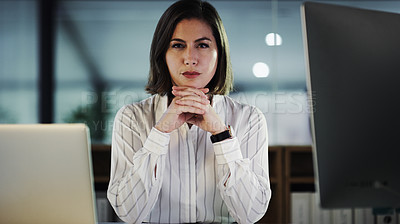 Buy stock photo Cropped portrait of an attractive young businesswoman looking serious while working late in a modern office
