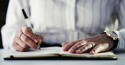 Buy stock photo Cropped shot of an unrecognizable businesswoman making notes in a notebook while working late in a modern office