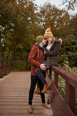 Buy stock photo Full length shot of an affectionate young couple spending time together at a park in late autumn