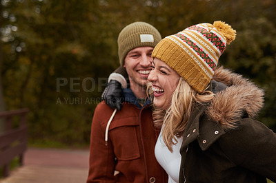 Buy stock photo Cropped shot of an affectionate young couple laughing together while standing in a park in late autumn