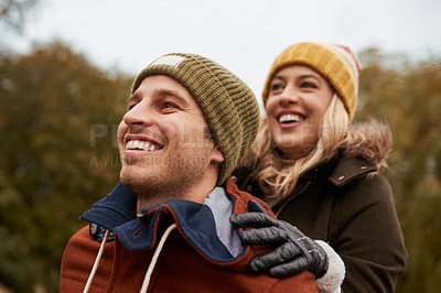 Buy stock photo Cropped shot of an affectionate young man smiling while piggybacking his girlfriend in a park in late autumn