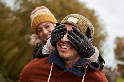 Buy stock photo Cropped shot of an affectionate young woman playfully closing her boyfriend's eyes in a park in late autumn