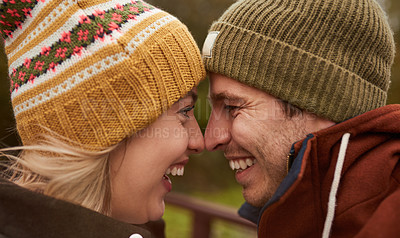 Buy stock photo Cropped shot of an affectionate young couple smiling at each other while standing in a park in late autumn