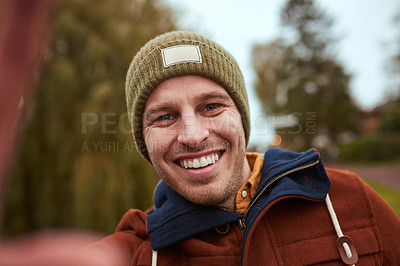 Buy stock photo Cropped portrait of a handsome young man taking a selfie while standing in a park in late autumn