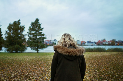 Buy stock photo Rearview shot of an unrecognizable woman walking through a park in late autumn